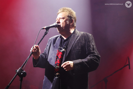 Jarek Janiszewski trzyma statyw do mikrofonu, do którego śpiewa.
